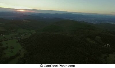 Aerial view of forest, grassland and town at sunset.