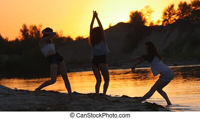 Three sexy girls dancing on the beach at sunset