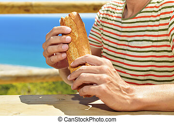 young man eating a sandwich outdoors - closeup of a young...