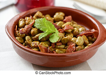 spanish broad bean stew with serrano ham - closeup of an...