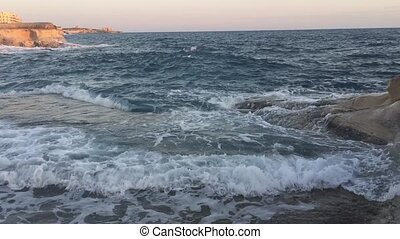 Rocky coast at sunrise - Choppy sea at sunrise seen from a...