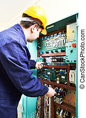 adult electrician builder engineer worker testing electronics in switch board