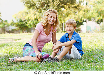 Young happy mother and little son sitting in park