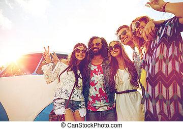 hippie friends over minivan car showing peace sign - summer...