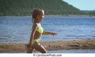 Cute little blonde girl running by a lake with the green...