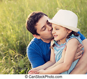 Happy father kissing her laughing daughter in hat on summer...