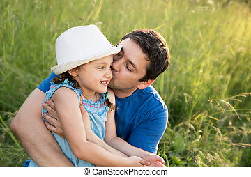 Happy father kissing her laughing daughter in hat on summer green grass background
