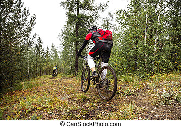 male athlete riding through in forest