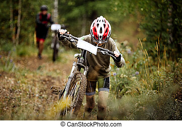 teen boy athlete mountainbike uphill on foot with his...