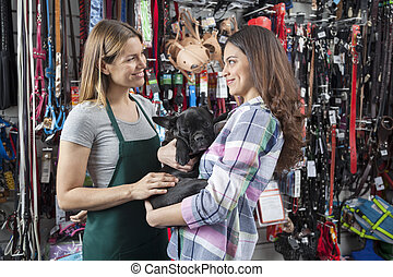 Saleswoman Looking At Female Customer Carrying French...