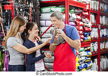 Happy Salesman Showing Rabbit To Family In Store - Happy...