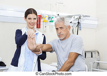 Female Doctor Examining Senior Mans Hand - Young female...