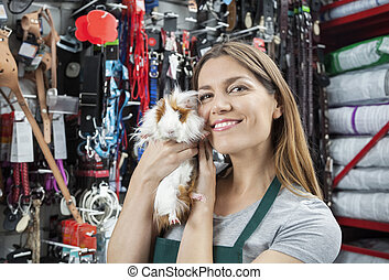 Beautiful Saleswoman Holding Cute Guinea Pig At Store -...