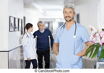 Confident Doctor Standing With Colleague And Patient In Backgrou