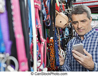 Customer Using Mobilephone While Buying Pet Leash - Mature...