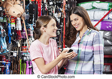 Mother And Daughter With Guinea Pig In Pet Store - Happy...