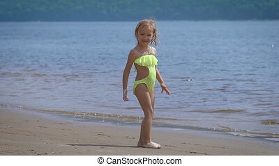 Cute little blonde girl having fun by a lake on warm and...