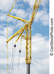 Large telescopic crane against cloudy sky - Large yellow...