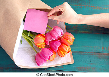 Tulip flowes bouqet with blanked card - Woman hand place a...