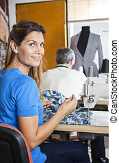 Portrait Of Confident Tailor Sitting At Workbench - Rear...