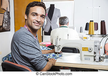 Portrait Of Smiling Male Tailor Using Sewing Machine - Side...