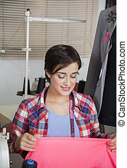 Smiling Tailor Holding Fabric At Workbench - Smiling female...