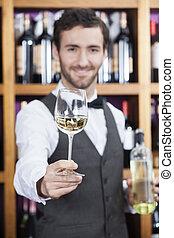 Bartender Offering White Wine Glass Against Shelves -...