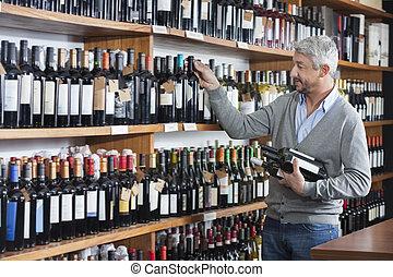 Customer Shopping For Wine Bottles In Store