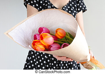 Woman holds warped Tulip flowers bouquet Women holidays...