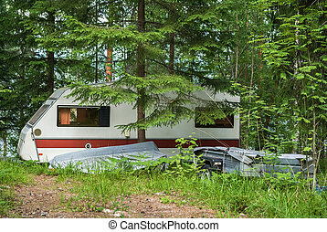 Trailer in forest - House-trailer parked in the forest, on...