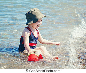 girl with hat and watering pot toy on beach sitting in water waves having fun