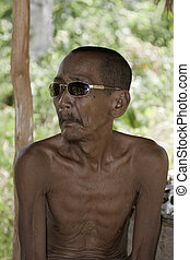 Old Indonesian Village Man sitting down thinking about his...