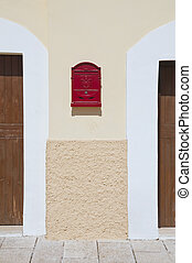 Red postbox between two doors.