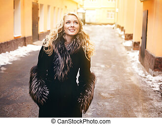blond girl with long curly hair in fur coat