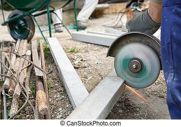 Construction worker cutting a reinforced concrete pillar for...