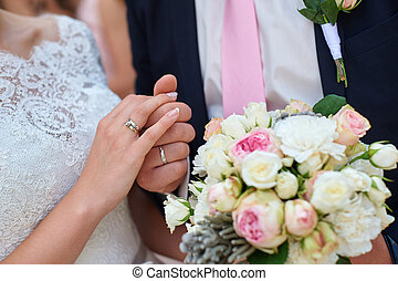 bride and groom holding hands with bridal bouquet