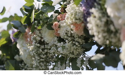 Close-up of part of wedding arch with pink and white flowers