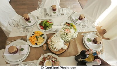 Beautifully decorated banquet table with flowers and different food snacks and appetizers with sandwich, wine glass, plate on corporate event or wedding celebration