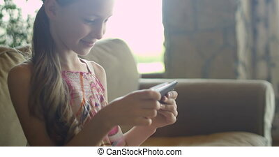 Little girl playing games or using app on tablet sitting on...