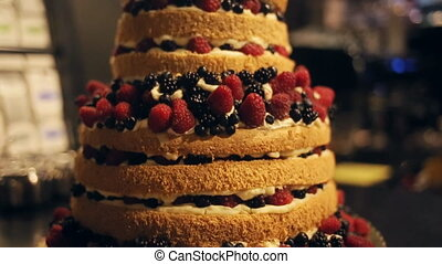 Gourmet tiered wedding cake decorated with berries at...