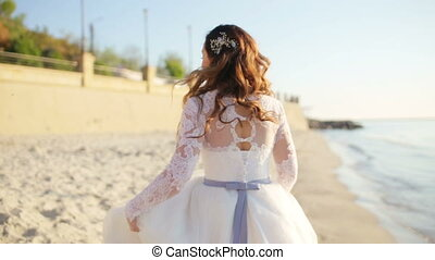 A beautiful bride standing on a cliff on the sea
