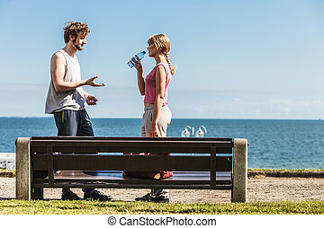 Man and woman drinking water outdoor Young couple taking...