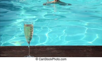 young happy woman drinks champagne in a swimming pool.