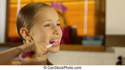Close-up of little smiling girl brushing teeth in the...