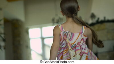 Rear view of a little girl with her soft toy running happily through the house with modern interior
