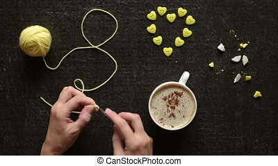 Female hands crocheting over the black board with a cup of...