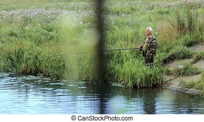 Fisher man with fishing rod catching fish on lake