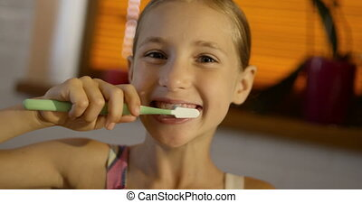 Little cute girl wearing pink pyjama brushing her teeth