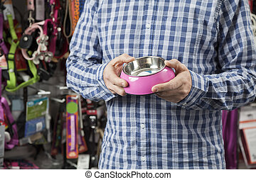 Midsection Of Customer Holding Pet Food Bowl - Midsection of...