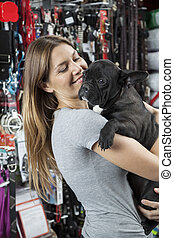 Woman Carrying French Bulldog In Store - Loving mid adult...